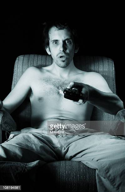 Captivated and Shirtless Man Sitting, Holding Television Remote