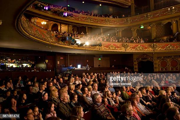 Captivated audience watches a performance of the pantomime Cinderella from the elaborately decorated stalls at the Hackney Empire Theatre. It is a...
