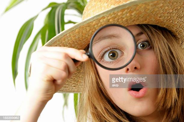Captivated girl looks through magnifier