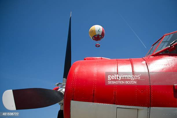 """Captive balloon is seen behind a parked propeller aircraft at """"Le Parc du Petit Prince"""" on June 26 in Ungersheim, eastern France. The main..."""