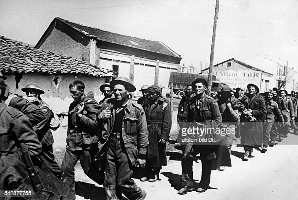 Captured British and Greek soldiers are marching through a village