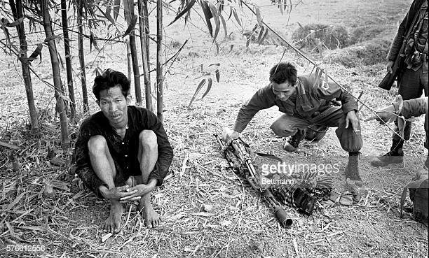 Captured Communist Viet Cong soldier glares at photographer as Vietnamese government folder inspects Russianmade carbine grenades and other arms the...