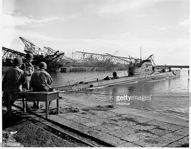 Captured Italian submarine in harbor at Naples Italy after the September 1943 action Bombed and scuttled ships in background October 6 1943