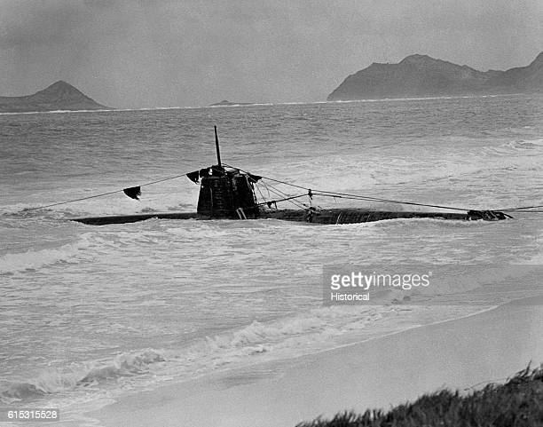 Captured Japanese two-person submarine rests in the wave off Bellows Field after the Japanese attack on Pearl Harbor.