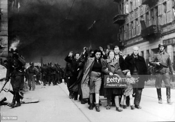 Captured Jewish civilians who participated in the Warsaw Ghetto Uprising are marched out of the city by Nazi troops Warsaw Poland April 19 1943