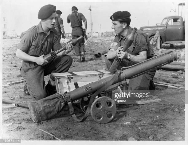 A captured Russian made rocket launcher used by infantry is viewed by Private Sam Kirvin of Manchester and Sergeant Norman Smith of Blackburn of the...