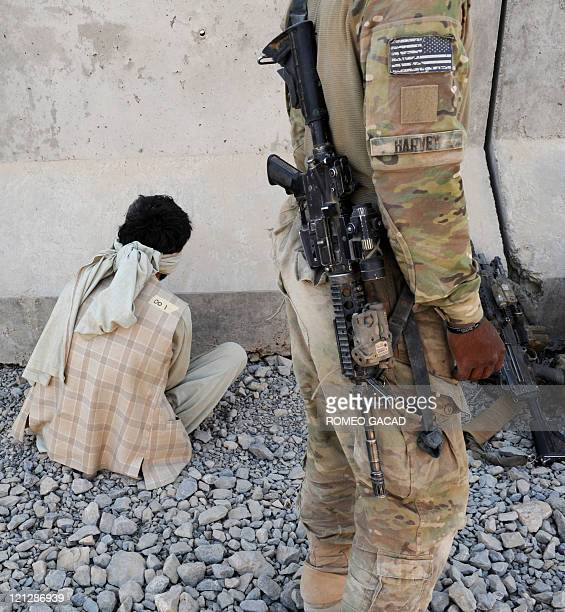Captured Taliban suspect identified as detainee number 1 awaits interrogation on arrival at the Forward Operating Base Pasab in Zahri district...