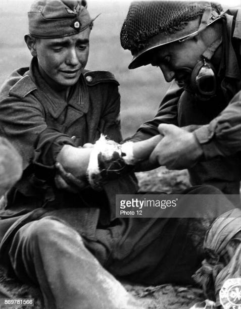 Captured, teenage, German soldier cries as he is treated for his wounds by an American soldier as they wait for a medic to arrive. From Cherbourg,...