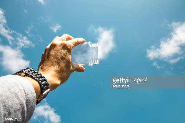 capturing the clouds from the sky with with glass pot in creative picture from personal perspective. - vorstellungskraft stock-fotos und bilder