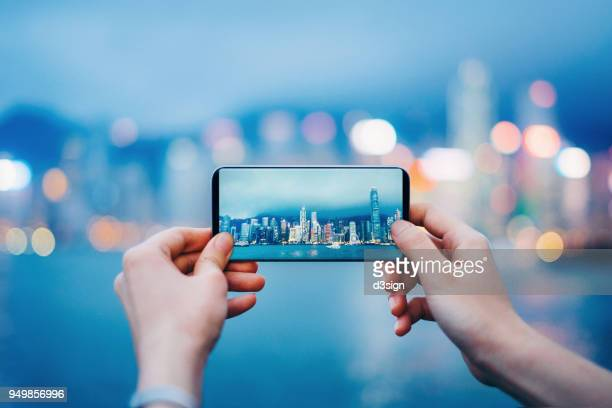 capturing the iconic city skyline of hong kong by the victoria harbour during sunset - photographing stock pictures, royalty-free photos & images