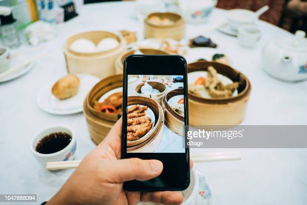 Capturing the snapshots of an enjoyable meal of dim sum with friends by smartphone in a restaurant