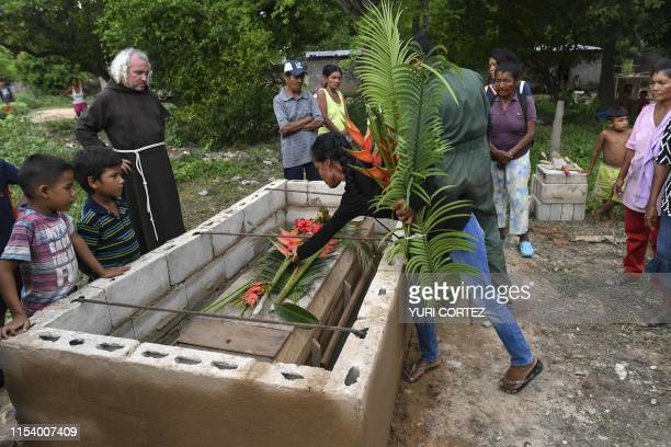 Capuchin friar Nelson stands next to relatives and friends of a Yukpa native who died due to a gastric ulcer during his burial at the cemetery of Los...