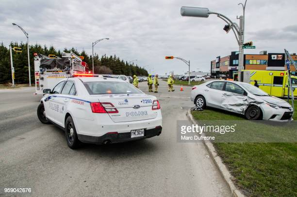 car accident at a road intersection with police car, firetruck and firemen in background - quebec stock pictures, royalty-free photos & images