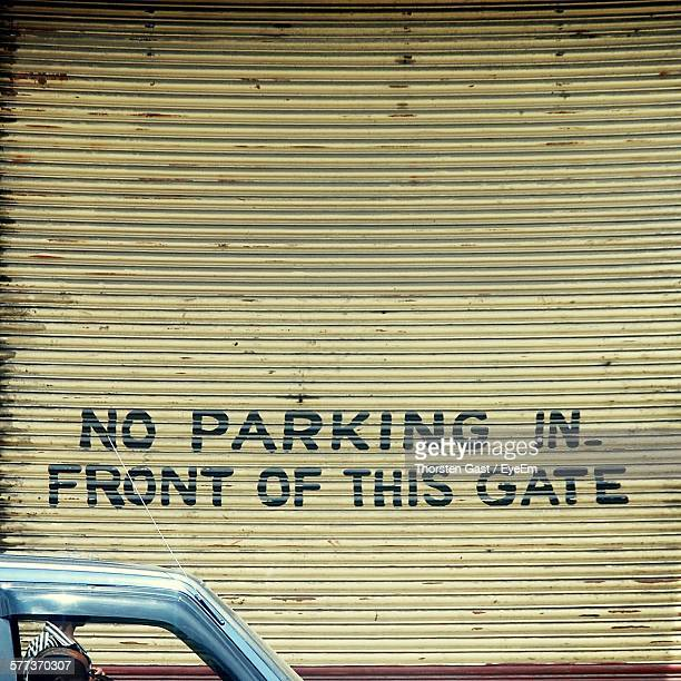 Car Against No Parking Sign On Corrugated Iron Shutter