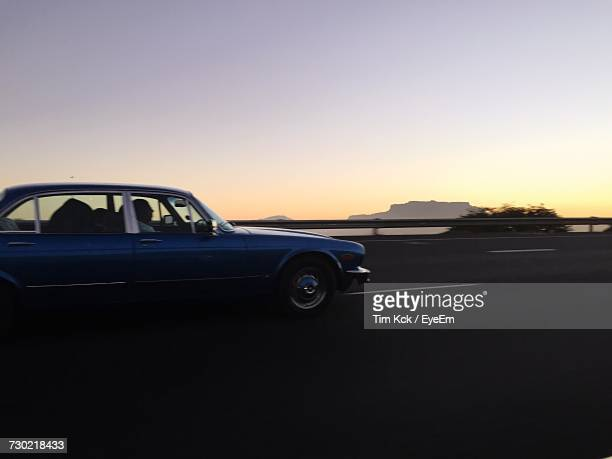 car against sky during sunset - vehicle light stock photos and pictures