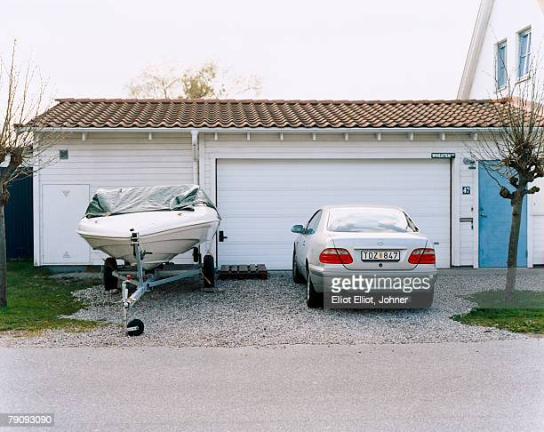 A car and a boat outside a garage.