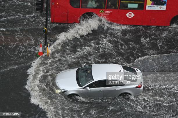 Car and a bus drives through deep water on a flooded road in The Nine Elms district of London on July 25, 2021 during heavy rain. - Buses and cars...