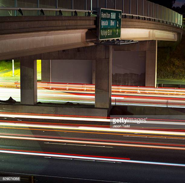 car and break lights under freeway overpass - jason todd stock photos and pictures