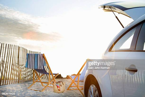 Car and deckchairs on the beach.