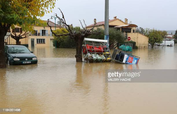 A car and gas tanks sit in water in a flooded area after heavy rains in Le Muy southeastern France on November 24 2019 Two people lost their lives...