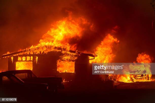 TOPSHOT A car and house are engulfed in flames as the 'Wall Fire' burns through a residential area in Oroville California on July 8 2017 The first...