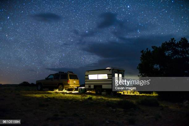car and illuminated travel trailer against star field - camper trailer stock pictures, royalty-free photos & images