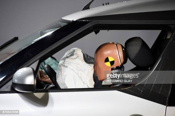 A car and its airbag are pictured after a frontal crash test with another car without a safety belt buckled in the back seat as part of France's Road...