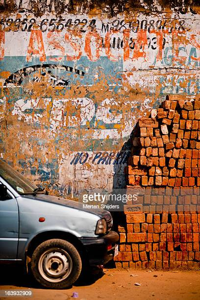 car and stacked bricks at eroded wall - merten snijders photos et images de collection