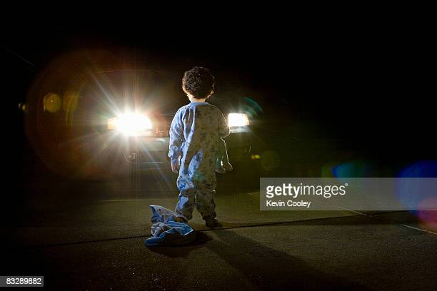 Car and toddler in driveway, night