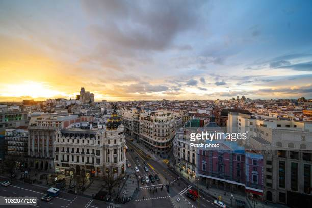 car and traffic lights on gran via street, main shopping street in madrid during sunset. spain, europe. - madrid stockfoto's en -beelden