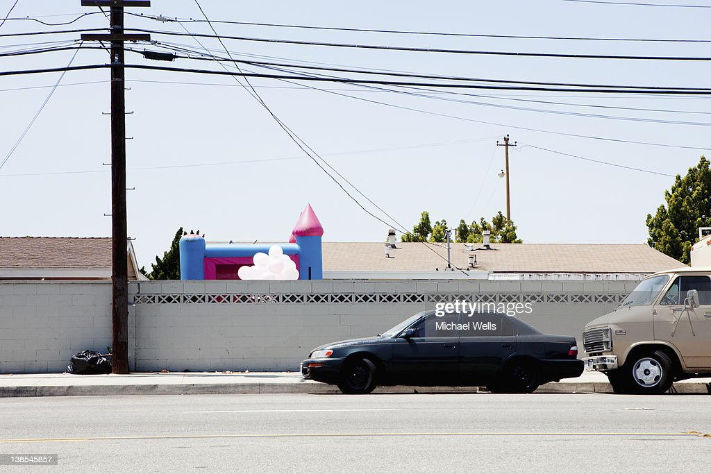 Car And Van Parked Next To Wall With Bouncy Castle In Background