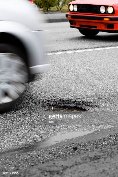 car approaches a pot hole - pothole stock photos and pictures