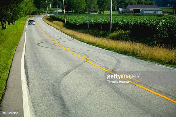 car approaches swerving tracks on a country road - timothy hearsum stock pictures, royalty-free photos & images