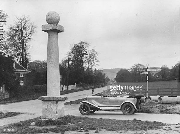 A car approches an old milestone at the road fork just before High Wycombe on the main London to Oxford road