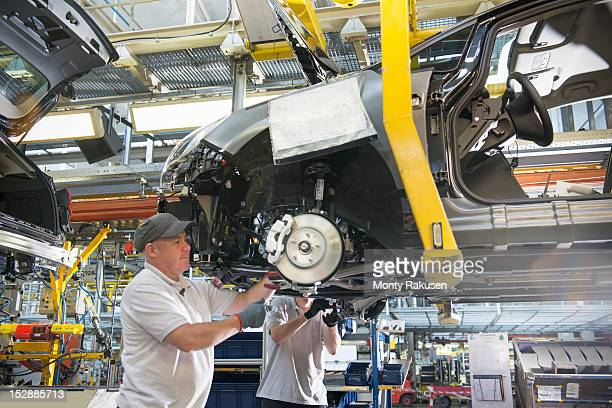 Car assembly workers fitting axles to cars on production line in car factory