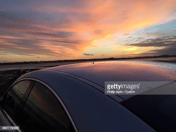 Car At Beach Against Cloudy Sky During Sunset