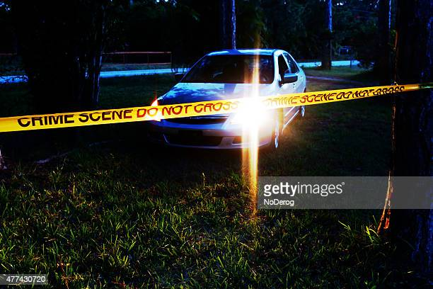 Car at crime scene in wooded area at night