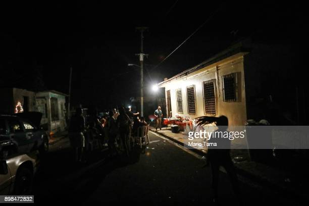 A car battery connected to an inverter and a generator provide power for a makeshift street party on a block without grid electricity on Christmas...
