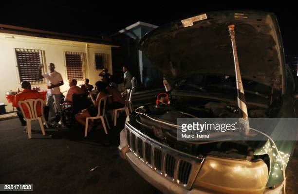 A car battery connected to an inverter provides power for a makeshift street party on a block without grid electricity on Christmas Eve on December...