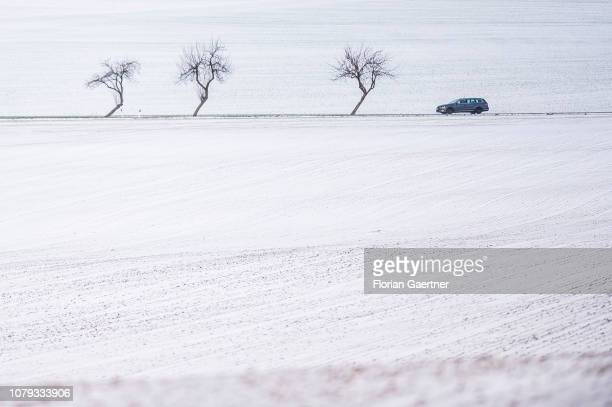 A car between snow covered fields is pictured near the germanpolishczech border triangle at the Zittauer Mountain on January 02 2019 in Zittau Germany