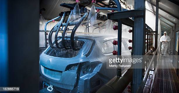 Car bodies being cleaned prior to spraying in car factory