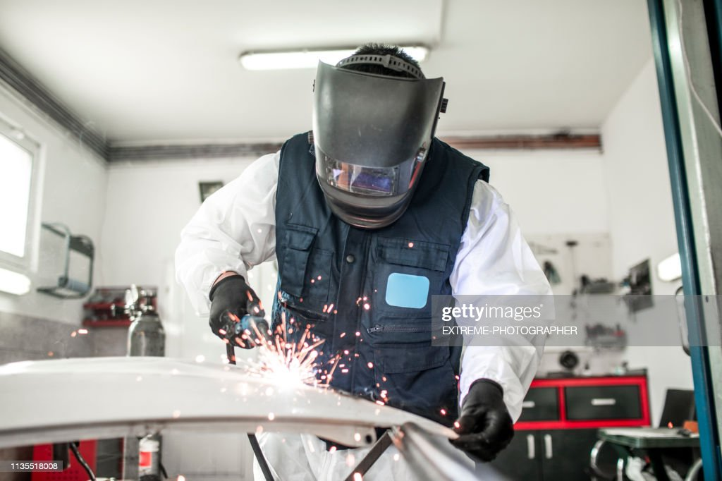 Car Body Shop Technician Using A Mig Welder To Repair A ...