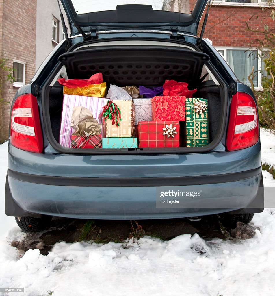 Car boot, filled with Christmas presents, snow underfoot : Stock Photo