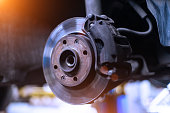 Car brake disk and caliper close up without wheel in cold colors with beautiful backlight