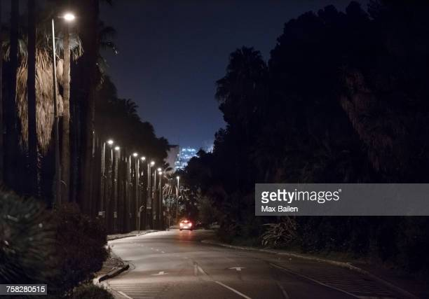 car break lights and street lamps on city road at night, barcelona, spain - film noir style stock photos and pictures