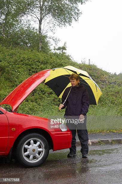 Car breakdown woman with umbrella waiting