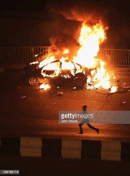 A car burns after being set alight by protesters near Tahrir Square during continued clashes between antigovernment demonstrators and supporters of...