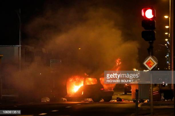 TOPSHOT A car burns after being set of fire overnight on November 19 2018 in SaintDenisdelaReunion on the French overseas island of La Reunion on the...