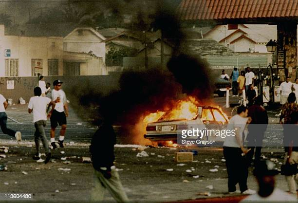 A car burns as looters take to the streets at the intersection of Florence and Normandie Avenues April 29 This intersection is considered the...