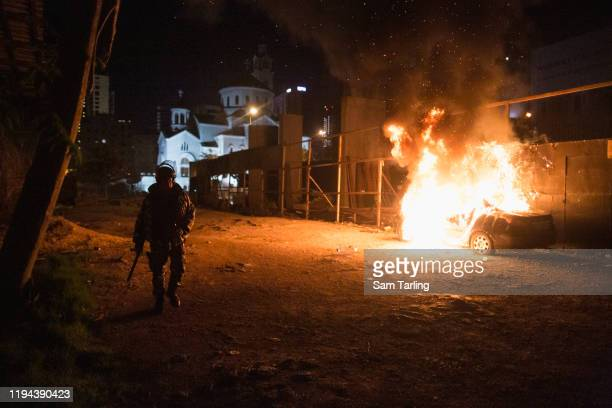 Car burns as supporters of Shia political parties clash with security forces in the early hours of December 17, 2019 in Beirut, Lebanon. The clash...